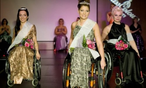 women in long gowns in wheelchairs with banners on them and tiaras