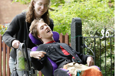 Personal assistant pushing disabled person in a wheelchair