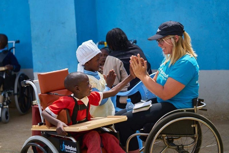 Arielle Rausin playing with disabled child in wheelchair