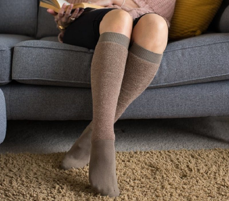 Woman sitting on a sofa wearing DermaTuff socks to protect thin skin
