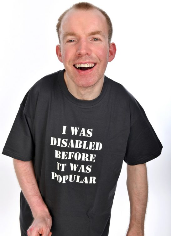 Lost Voice Guy Lee Ridley in a TV shirt saying I was disabled before it was popular
