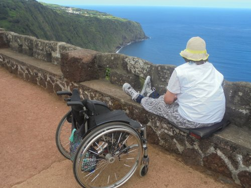 Wheelchair user sat on wall looking over lake in Azores
