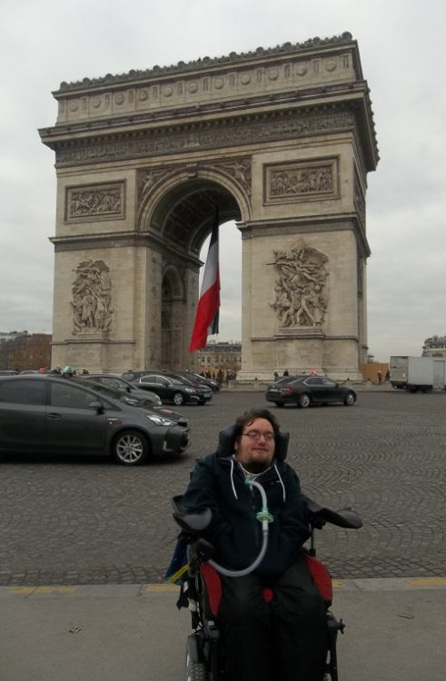 Wheelchair user Derry Felton in front of the Arc de Triomph