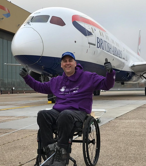 Andy Knight in his wheelchair in front of British Airways plane