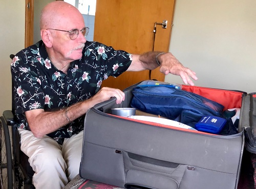 Disabled traveller Wolf packing his suitcase for holiday