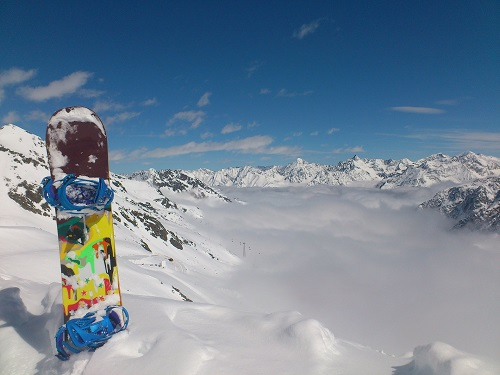 Snowboard on top of snowy mountains