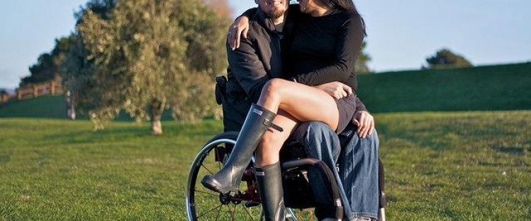 Woman sat in the lap of a man in a wheelchair