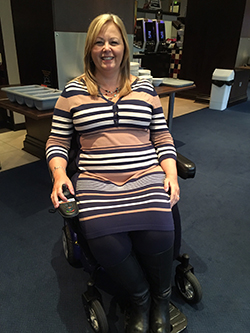 Lynley Adams in wheelchair at the office