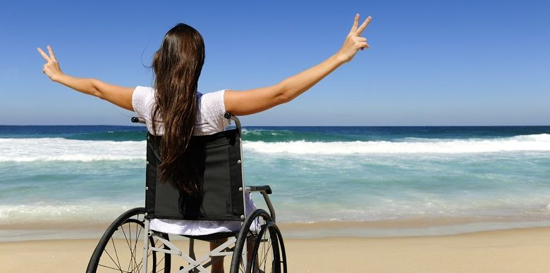 Disabled woman in wheelchair on beach