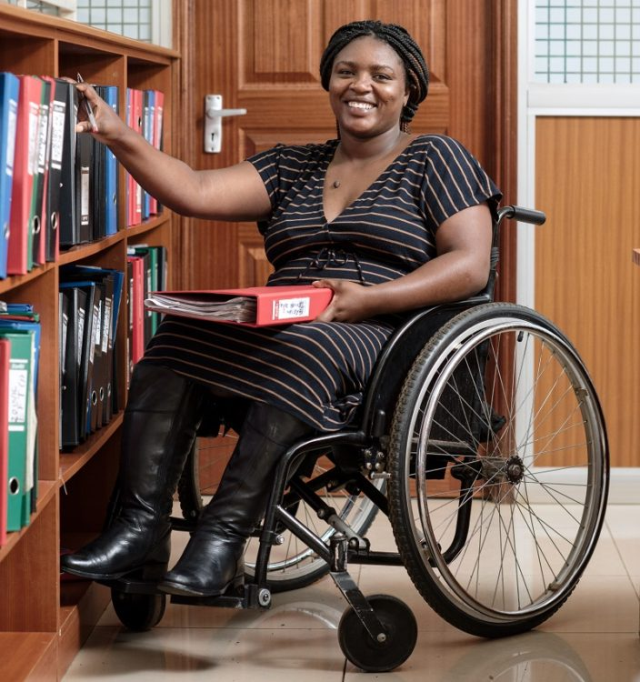Salome in a library in her wheelchair from Motivation