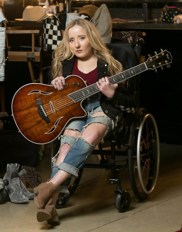 Disabled musician Ali McManus in her wheelchair holding a guitar