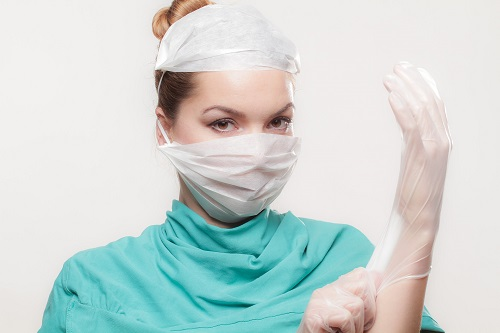 Nurse with gown, face mask, hair net and rubber gloves on