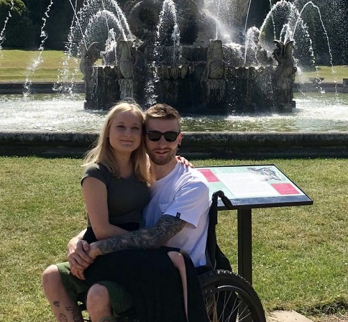 Becky sitting on Dan's lap in his wheelchair in front of a fountain