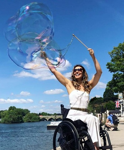 Samanta Bullock blowing bubbles by a lake in London