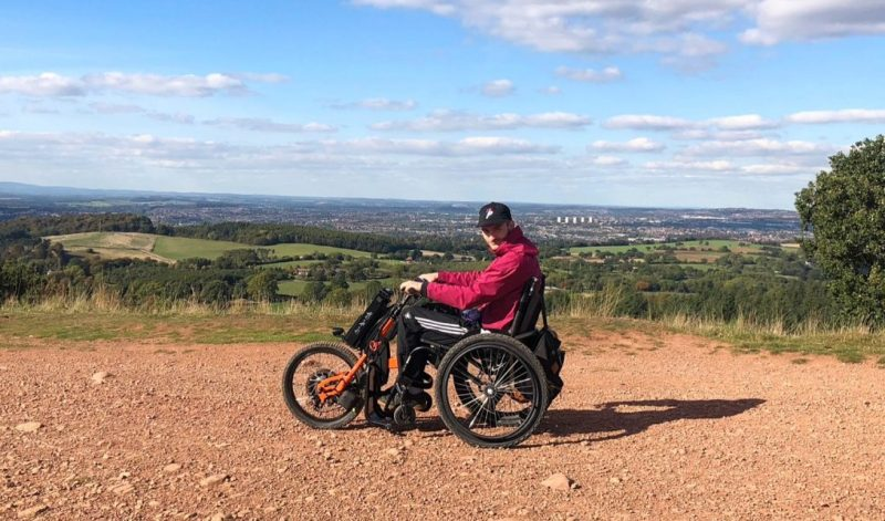 Dan in a wheelchair trike on a hilltop