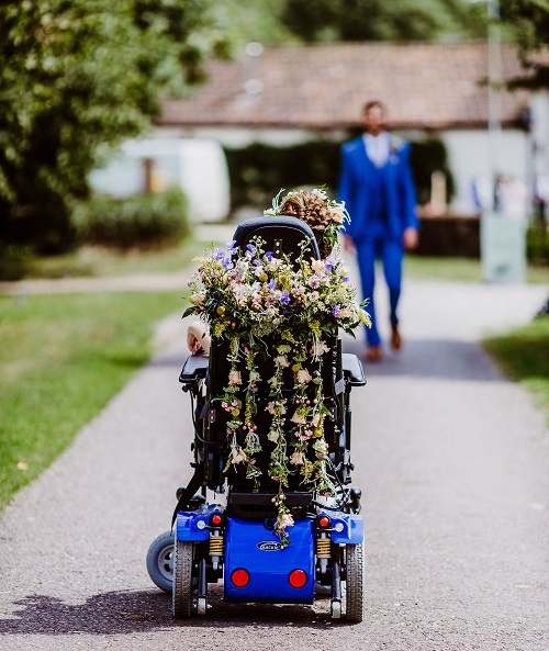 Tori's wheelchair from behind covered in flowers on her wedding day