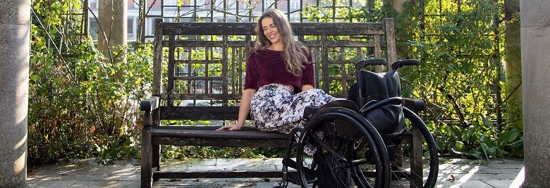 Disabled model Samanta Bullock sat on a bench with legs resting on wheelchair