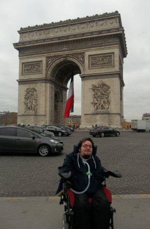 Wheelchair user Derry Felton in front of the Arc de Triomph
