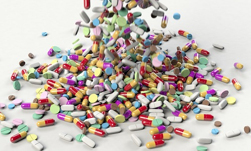 Lots of pills being tipped onto a pile