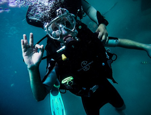 Man scuba diving with a guide