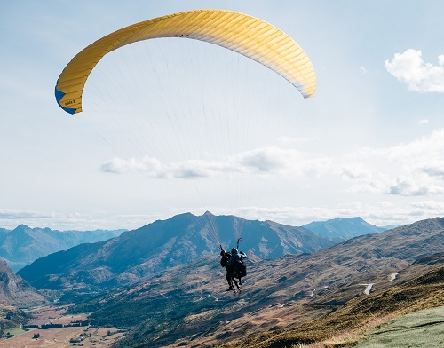 Two people gliding over mountains