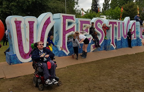 Alex Squires at Isle of Wight festival in front of a festival sign