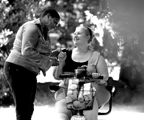 Personal assistant with woman using a mobility scooter