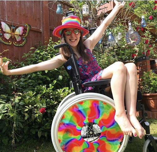 Rebecca Sullivan with rainbow wheels on her wheelchair