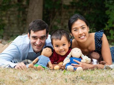 Rafael Tselikas, son Alex and Winnie Mak smile at camera holding three soft toys