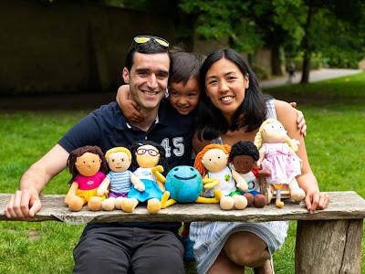 Rafael Tselikas, son Alex and Winnie Mak smiling at camera holding six disability dolls
