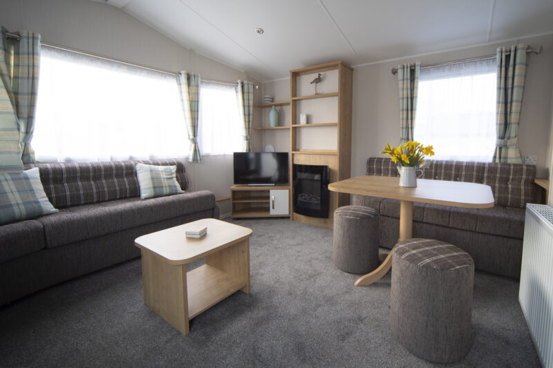 Accessible caravan lounge with sofa, coffee table, TV, electric fireplace and dining table