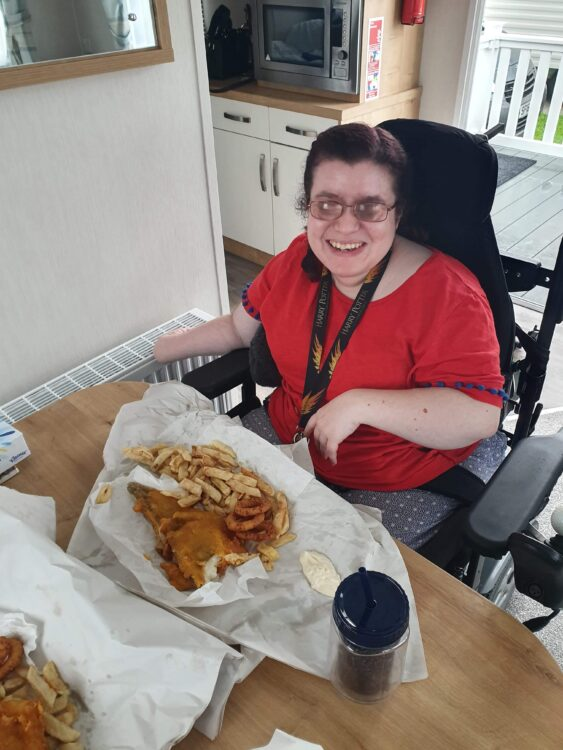 Emma sat at the table in accessible caravan eating fish & chips