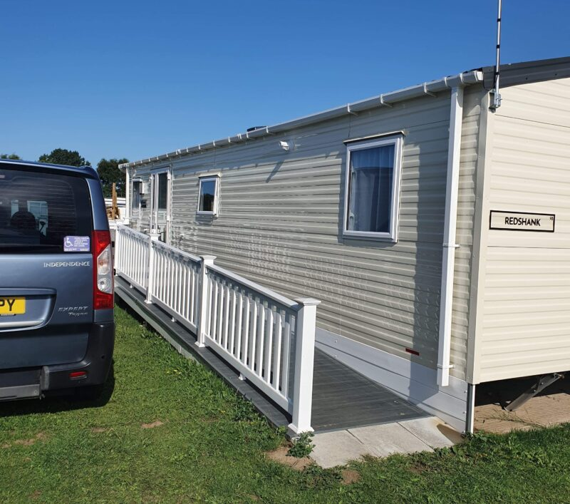 Front of accessible caravan with accessible ramp and car park space