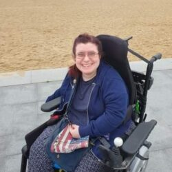Emma sat by sandy beach in er wheelchair