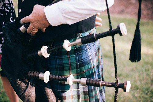 Bagpipes being held by a man wearing a kilt