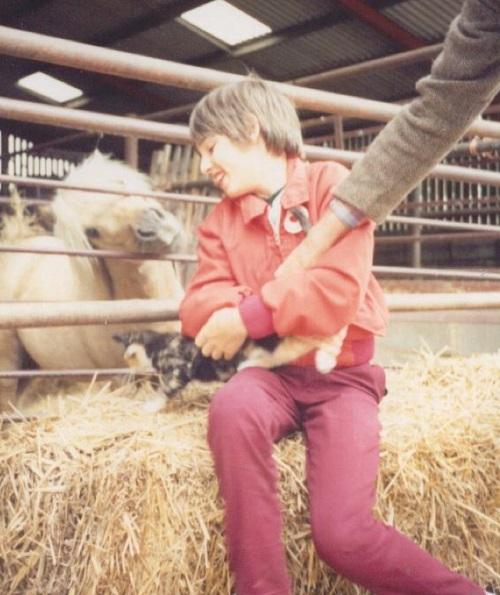Disabled activist Simon Stevens as a child sat on a hay bail at a farm