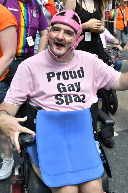 Disabled activist Simon Stevens at Gay Pride in a pink t-shirt with the words 'Proud gay spaz'