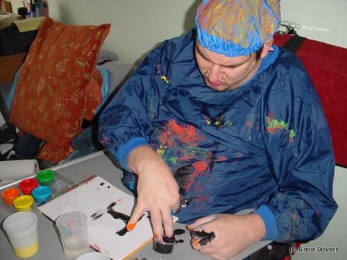 Disabled activist Simon Stevens painting