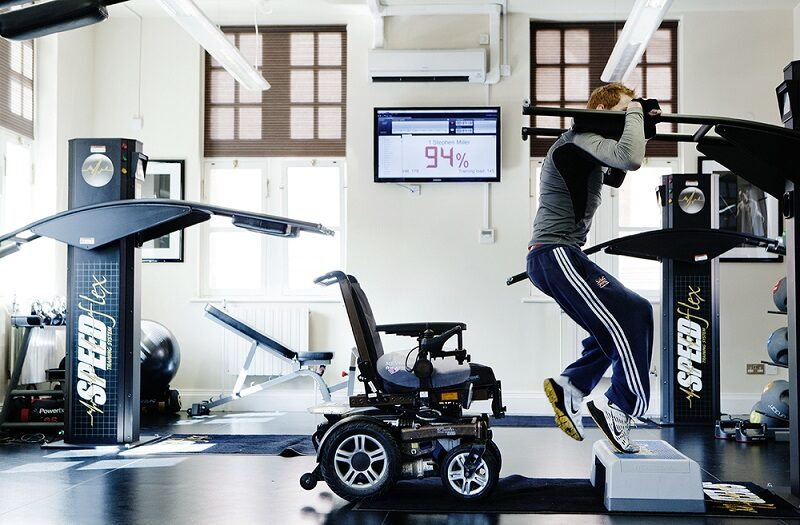 Paralympian Stephen Miller in a gym on an exercise machine with wheelchair behind him