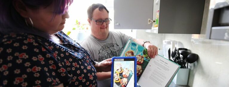 Man with Downs Syndrome looking at app MyLife app in kitchen with carer