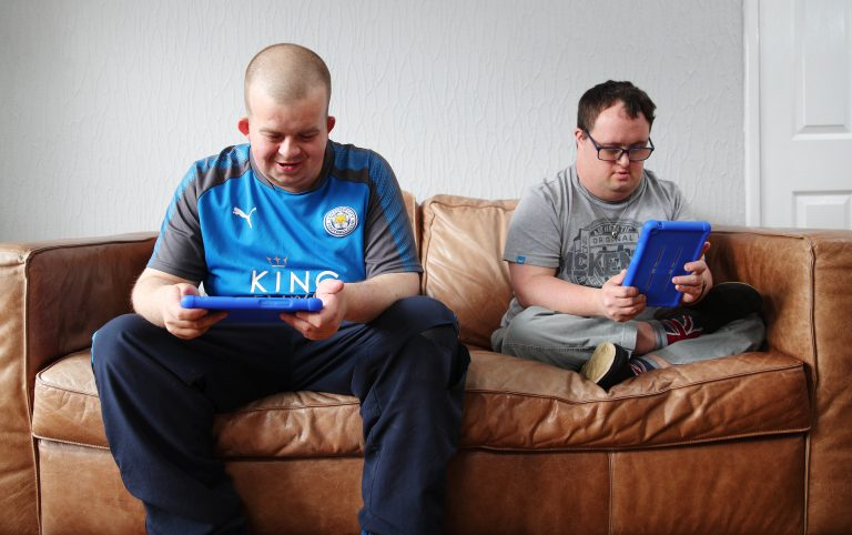 Two men with Down's Syndrome using the Vodafone and Mencap MyLife app on their tablets sat on a sofa