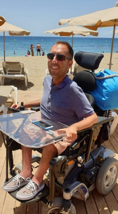 Wheelchair user Martyn Sibley on an accessible beach in Tenerife with Limitless Travel