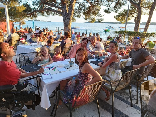 Wheelchair user Martyn Sibley with his fiance and family in Croatia having dinner looking over the sea