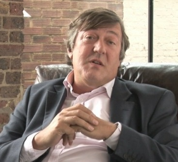 Stephen Fry sat in an armchair talking