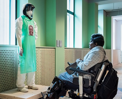 Woman in a wheelchair looking at a dummy in a medical uniform