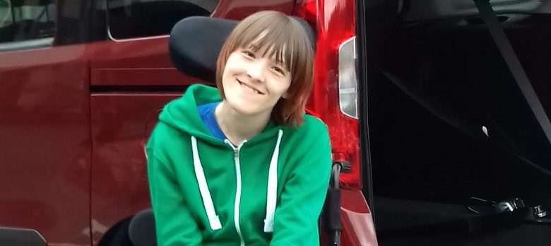 Ailsa in her electric wheelchair outside her car