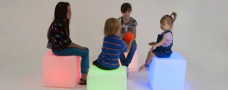 Children with autism playing with a sensory ball sat in a circle