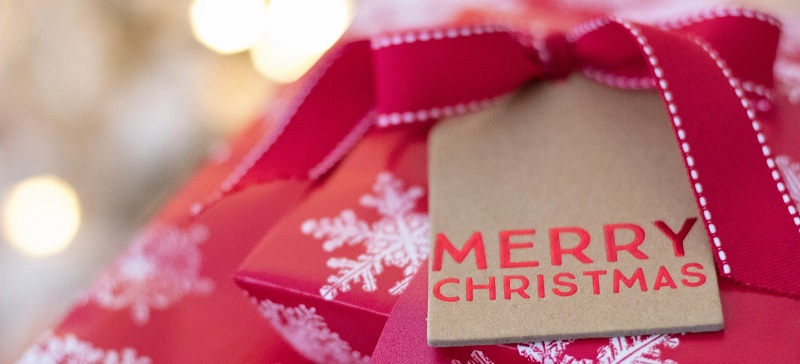 Christmas presents in red wrapping paper with snowflakes and a tag saying Merry Christmas