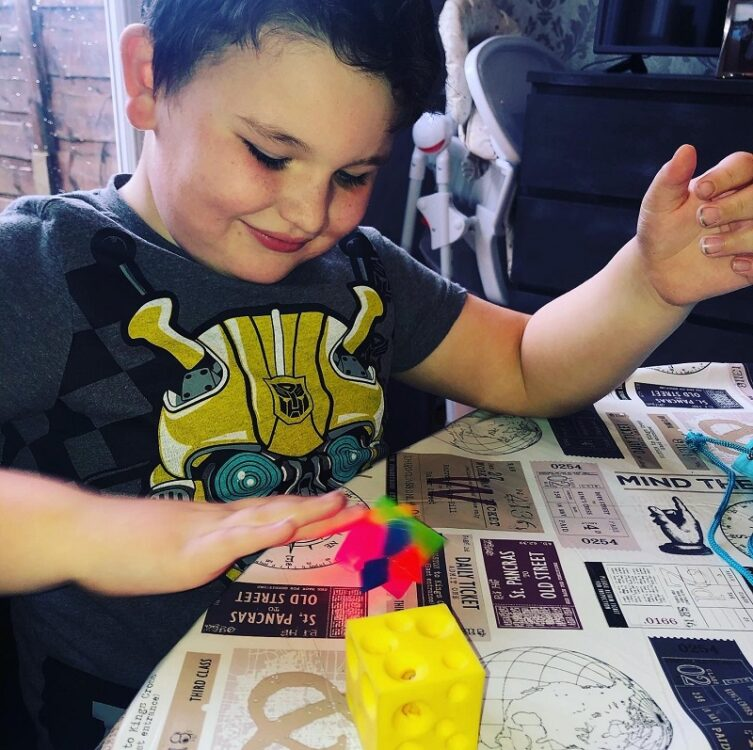 Leo sat at a table playing with sensory toy for people with autism