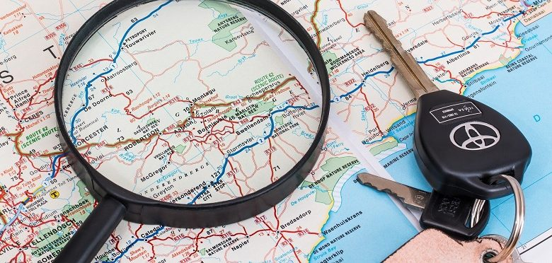 Map with magnifying glass and car keys on top